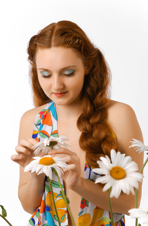 Youth woman is looking at a chamomile and plucking its petals