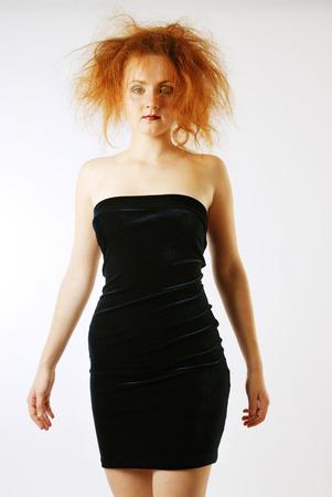 velvet dress: The pretty girl is wearing a velvet strapless dress  She has made up her face  Her red hair is backcombed