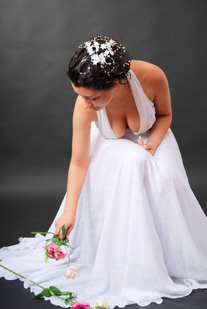 Happy bride is sitting and picking up flowers