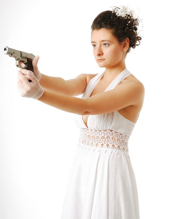 Pretty bride is aiming a silver pistol in the standing position   photo