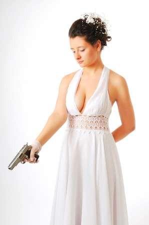 Pretty bride is aiming a silver pistol downwards in the standing position  White low-necked dress accentuates her beautiful shoulders and bosom  Her dark hair are arranged and decorated with white flowers  photo