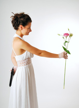 Pretty bride is reaching out a gentle flower and hiding a black handgun behind back  White low-necked dress accentuates her beautiful shoulders and hands  Her dark hair are arranged  photo