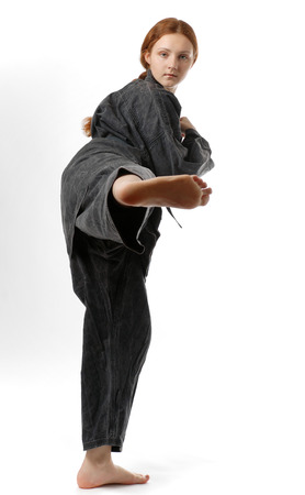 A teenage girl kicks her right legs  She is wearing a black kimono  photo