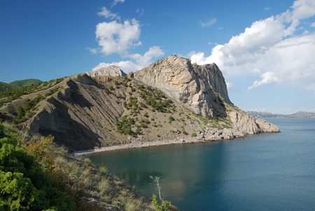 promontory: The promontory juts far into the sea  It forms a beautiful bay  The blue sky is reflected with the tranquil sea