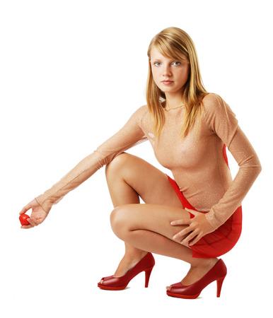 squatting: Una adolescente est� en cuclillas y mirando la c�mara La rubia lleva un vestido transparente y bombas rojas Ella est� sosteniendo un peque�o coraz�n artificial en la mano derecha