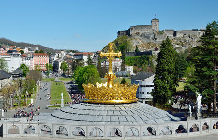 surmounted: Lourdes is a major place of Roman Catholic pilgrimage  There is a dome of the Rosary basilica surmounted with the gilded crown and the cross in the foreground   Stock Photo