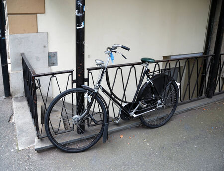 leant: Town bicycle is leaned against metal fence