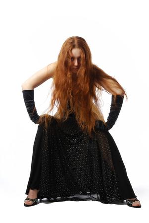 jambes �cart�es: Jeune femme est assise et pench� en avant Elle se tient avec les jambes �cart�es et met ses mains sur les hanches cheveux rouge en vrac est couvert visage Elle est v�tue d'une robe noire et des gants noirs