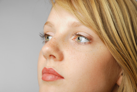 Young blonde has smooth skin freckled, full lips and large grey eyes  Copy space is on the left  She is looking sideways