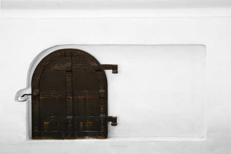Old wooden door is hinged on white wall  Ancient entrance is armoured with rusty iron stripes  photo