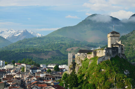fastness: An ancient stronghold dominates on the green rock above the famous town Lourdes in the French Pyrenees  Stock Photo