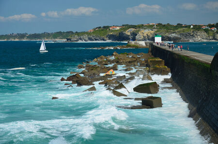 pays: Many vacationers are walking along the seawall at low tide in the vicinity of Saint-Jean-de-Luz