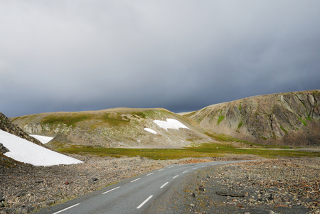 morose: Asphalt road is running past mossy rocks with snowfields  This is the road to Hamningberg  Highway of the north Norwegian coast is opened up only two summer months  Stock Photo