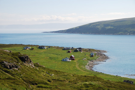 inclement weather: Small fishing village is located on the side of blue fjord  Mageroya is photographed in summer  There are wooden houses on the green moss and a lot of blue water