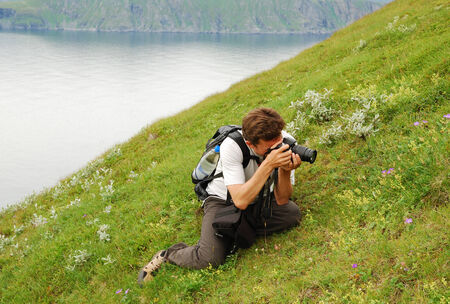Man is photographing flowers in green grass  He is sitting in the blooming slope of summer Soroya   Stock Photo