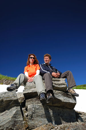 A woman and a man are sitting on the rock  They are photographed from below against the blue sky  There is a white snowfield behind them  Couple of tourists are resting  photo