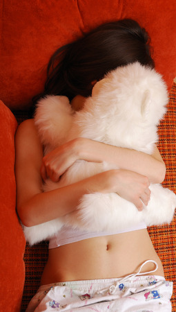 cuddly toy: Teenage girl is lying in the sofa bed and folding in both arms a soft toy  She is wearing pajamas  She is hidden with the cuddly toy  She is sleeping