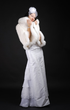 muffle: Graceful bride is standing and looking at camera  Pretty woman is wrapping up in a fur coat  She is wearing a white dress and a lady Stock Photo