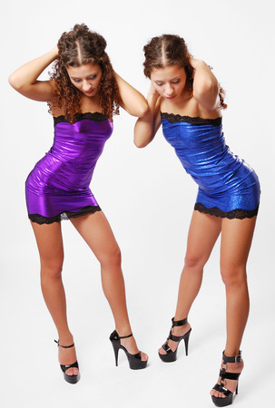 curly headed: Two young women are standing side by side and looking downwards  Pretty twins pick up her curly hair  They are wearing the same short shining dresses decorated black lace  Her slender legs are planted apart on high stiletto heels   Stock Photo