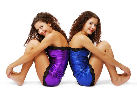 curly headed: Two young women are sitting back to back and looking at camera  Pretty twins pull up their legs equally  They are curly-headed and barefooted  They are wearing the same shining dresses