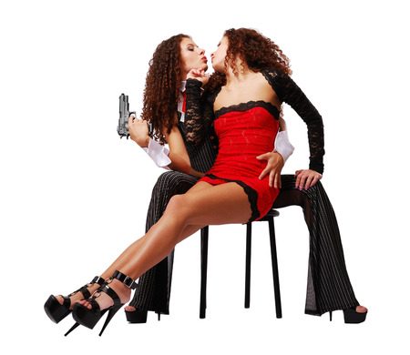 constraint: Two young women are sitting on the one chair  Pretty twins are about to kiss  One of them is holding a handgun and clasping the other  Their slender legs are on high stiletto heels
