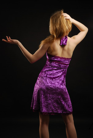 cocktaildress: Teenage blonde girl is standing back in the dark  She is wearing a velvet cocktail dress   Stockfoto