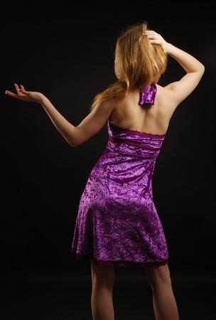 velvet dress: Teenage blonde girl is standing back in the dark  She is wearing a velvet cocktail dress   Stock Photo