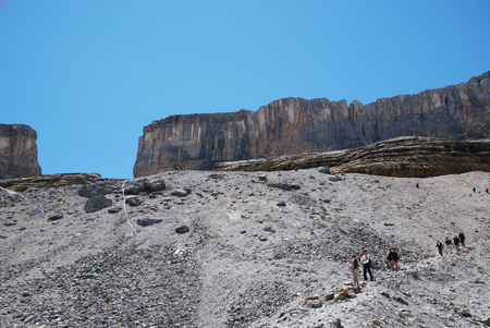 talus: Tourists are climbing to the Breche  La Breche de Roland is a natural gap in the steep cliffs of the Cirque de Gavarnie in the Pyrenees  The pathway passes through a scree