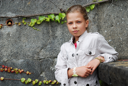 twined: Pre-teen girl is leaning on the parapet and looking seriously at the camera. She is photographed against the gray stone wall twined with ivy.