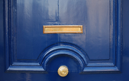 Shining surface of massive blue door decorated golden mail slot and round handle, close-up