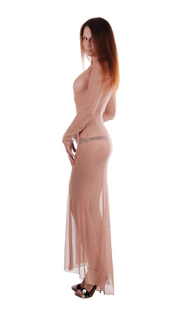transparent dress: Long-haired girl stands sideways and looks over shoulder, isolated on white