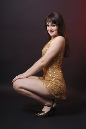 cocktaildress: Donkerharige model in glanzend cocktail jurk, gehurkte houding, opgetogen stemming Stockfoto