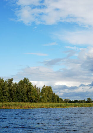 gusty: Azure sky with different clouds above rippled river, overgrown banks, windy weather