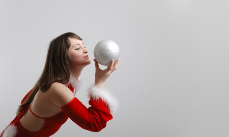 velvet dress: Pretty girl bending to silver christmas ball, red velvet dress with white down list, copy space on the right