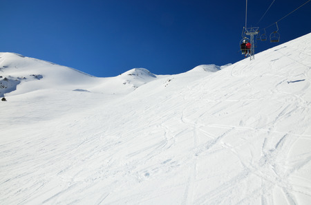 transported: People are being transported with a chair lift above the snowy slope in the winter Pyrenees.
