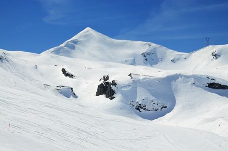 ski runs: A lot of ski runs on the snowy downhills against the blue sky and a peak in the winter Pyrenees. Stock Photo
