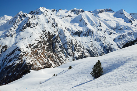 ski runs: A lot of ski runs on the snowy downhill against the blue sky and the mountain range in the winter Pyrenees.