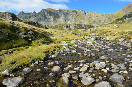 watercourse: Mountain watercourse runs to the alpine Ayous lakes in the highland of the Atlantic Pyrenees. There is the peak Larry in the background.
