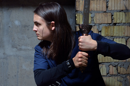 animation teenagers: A serious teenage boy is stealing along the wall of the abandoned building. He holds the sword.