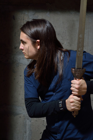 self contained: A serious teenage boy is stealing along the wall of the abandoned building. He holds the sword both hands. Stock Photo