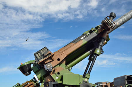 flak: The modern antiaircraft gun is photographed against the sky with a military helicopter.