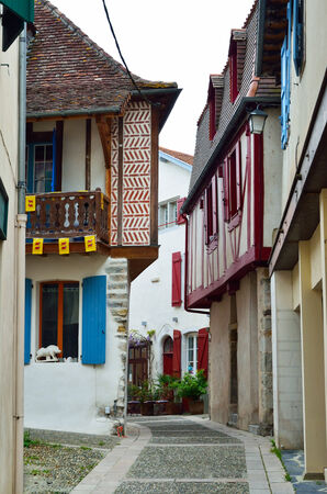 fachwerk: There are fachwerk houses with wood balconies and shutters in the narrow, curve street of the French town Salies de Bearn.