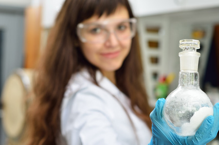 personnel matters: A young researcher holds a flask with a substance in the chemical laboratory. She is wearing an overall, protective gloves and glasses. Stock Photo