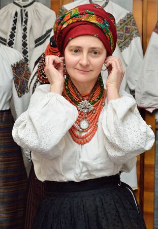 perls: The woman is dressing up a Ukrainian vintage national clothes. Stock Photo