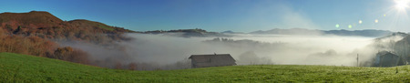 shrouded: The farm with a green pasture is situated on the forested mountain in the Pays Basque. The slopes are shrouded with mist in the winter sunny day. Stock Photo