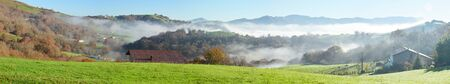 shrouded: The farms with a green pasture are situated on the forested mountain in the Pays Basque. The slopes are shrouded with mist in the winter sunny day.