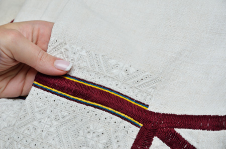 homespun: A female hand holds the white homespun linen sleeve with handmade embroidery.