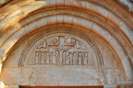 semicircular: The semicircular wall is decorated with the religious imagery over an entrance of the extant temple in the medieval village Siurana.
