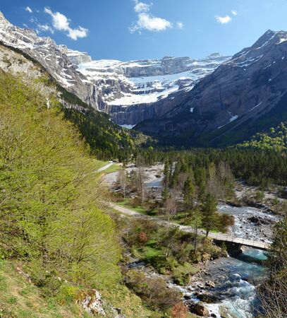 gave: Spring mountains are photographed in the valley to the cirque of Gavarnie. This is a large rock amphitheater. In the foreground a river Gave de Pau is running on the green mountainside.