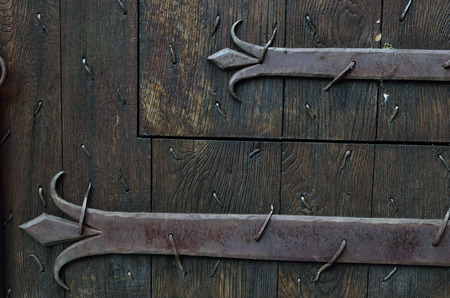 armoured: Old wooden door is armoured with iron stripes.